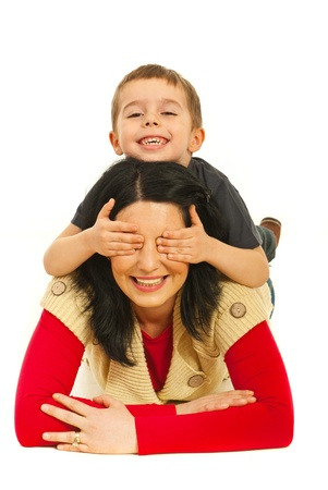 Piled family having fun and the boy covering eyes with hands to his mother isolated on white background Foto de archivo