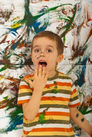 Surprised messy boy  after painting with hands a wall Stock Photo - 12595737