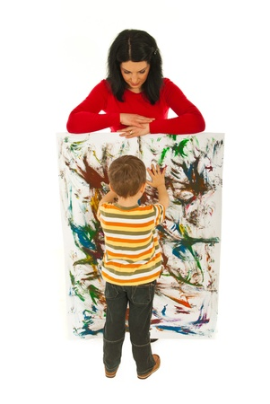 Mother watch her litlle boy who is painting a wall  with his hands isolated on white background photo