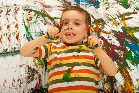 Messy painted boy pointing up and lying down on painted background Stock Photo - 12595738