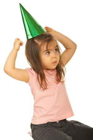 put away: Girl looking away and trying to put a green party hat on her head isolated on white background