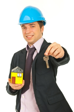Happy architect holding miniature house and giving keys isolated on white background,selective focus on keys photo