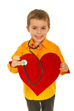 Happy  future doctor boy holding stehoscope and examine  a big heart shape isolated on white background photo