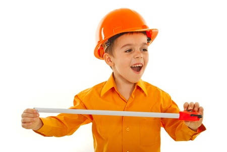Cheerful builder kid boy with orange helmet holding measure tool and looking away isolated on white background photo
