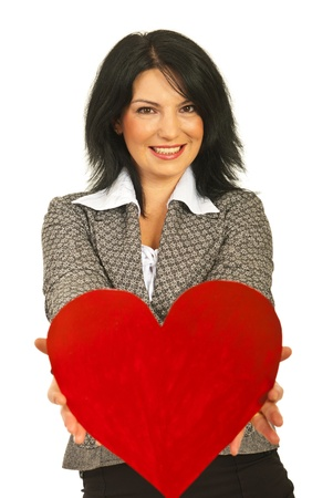 give: Smiling business woman offering a big heart isolated on white background