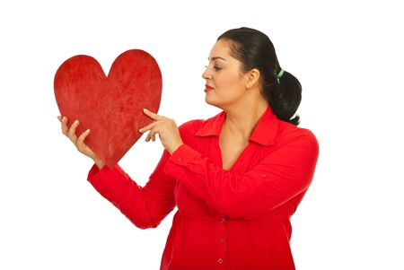 Woman in red clothes holding big heart and looking to object isolated on white background Stock Photo - 12595744