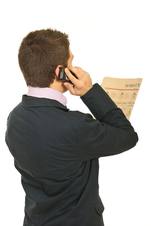 Back  of business man standing in semi profile reading newspaper and talking by phone mobile isolated on white background Stock Photo - 12595758