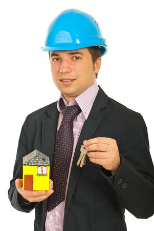 Engineer man holding miniature home and keys isolated on white background photo