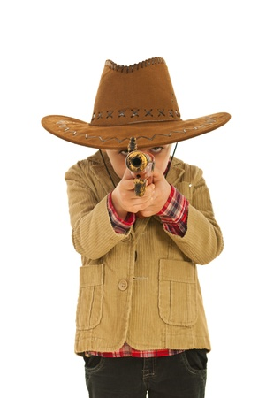 Little kid cowboy playing with weapon isolated on white background photo
