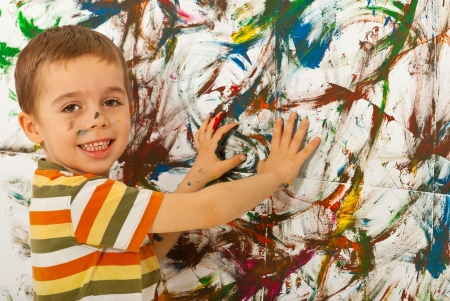 messy kids: Happy child boy painting a wall with his palms  Stock Photo