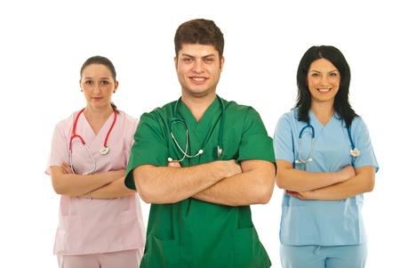 mani incrociate: Allegro gruppo di tre medici in piedi con le braccia piegate isolato su sfondo bianco Archivio Fotografico