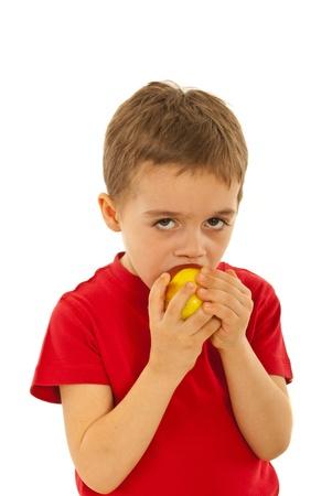 bit background: Child boy biting apple isolated on white background Stock Photo