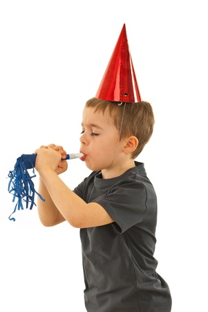 noise maker: Profile of little boy with party hat  strong blowing in a noise maker and holding his eyes closed isolated on white background Stock Photo