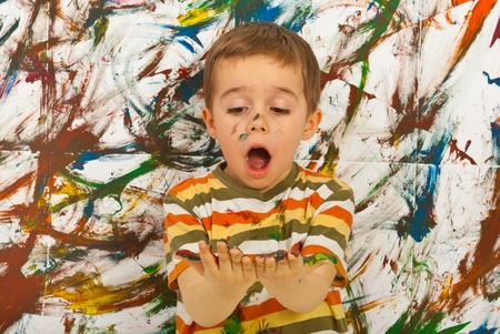 Surprised child boy looking at his messy palms  against painted background photo