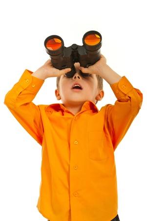 Ragazzo sorpreso guardando attraverso siolated binocolo su sfondo bianco Archivio Fotografico
