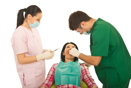 Dentist and his assistant working with patient woman isolated on white background photo