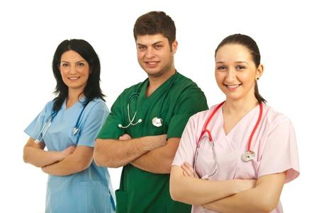Uomo allegro dottore nel mezzo di due infermiere sorridenti piedi in una linea con le braccia conserte isolato onw sfondo Hite