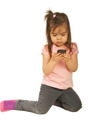 old cell phone: Toddler girl typing sms text message and sitting on the floor isolated on white background