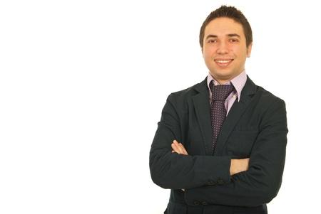 mani incrociate: Ritratto di uomo d'affari felice in vestito in piedi con le mani incrociate su sfondo bianco, copia spazio per il messaggio di testo nella parte sinistra dell'immagine