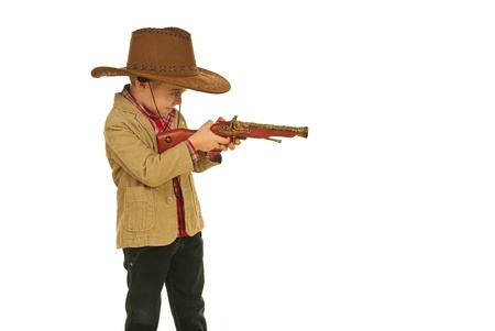 Little cowboy  shooting with weapon toy in profile isolated on white background photo