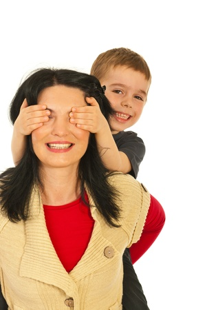 Happy mother giving piggy back ride to her son and the boy covering her eyes with palms isolated on white background photo
