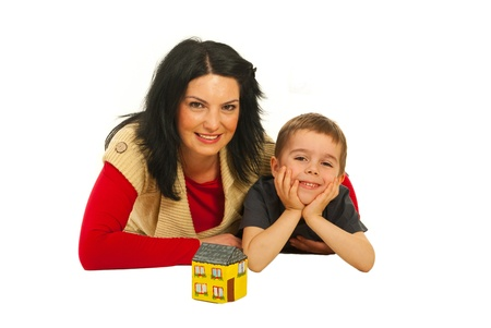 Happy mother and son lying on floor with a miniature home isolated on white background photo