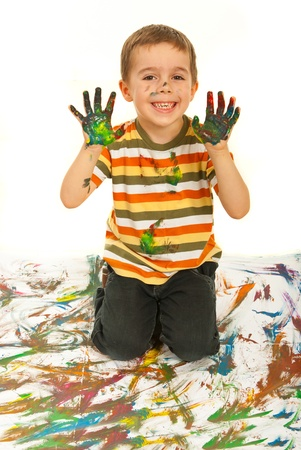 naughty boy: Laughing messy kid boy showing his colorful palms  over white background Stock Photo