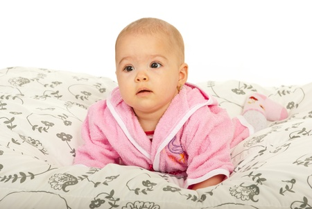 Cute baby girl in bathrobe crawling in bed against white background photo