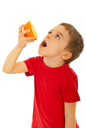 squeeze: Small boy squeeze orange juice to his mouth isolated on white background