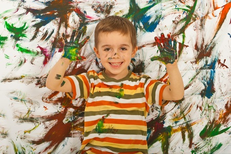 Happy messy boy showing colorful painted palms against painted background Stock Photo - 12596427