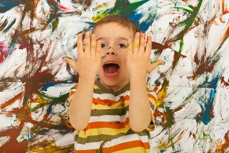Messy kid screaming and showing his hands  against painted background Stock Photo - 12596425