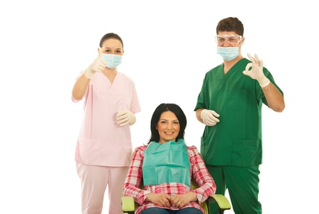 Happy dentists doctor and nurse showing okay and thumb up around smiling patient woman on chair isolated on white background photo