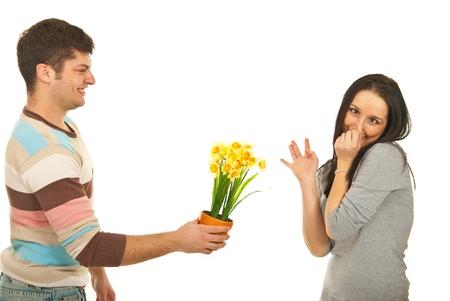 tufo: Oferta individuo narciso de flores a una mujer exigente, que hace caras y pellizcando la nariz para evitar el olor de flores aisladas sobre fondo blanco