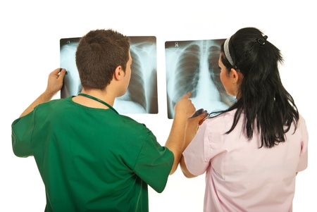 green back: Back of two doctors checking X-rays isolated on white background Stock Photo