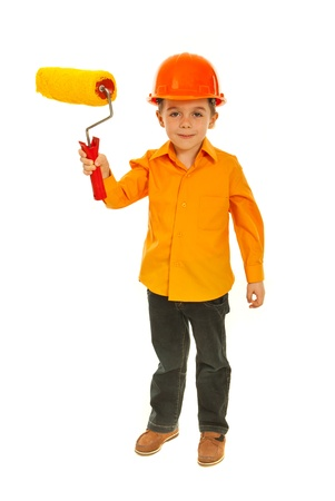 Full length of kid boy showing paint roller isolated on white background photo