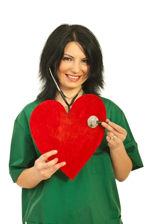 heart doctor: Happy smiling doctor woman examine heart shape isolated on white background