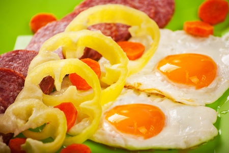 Close up of fried eggs with salami and vegetables on green dish Stock Photo - 12596516