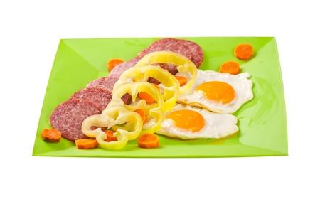 huevos fritos: Huevos fritos con salami decorado con verduras en la placa verde sobre fondo blanco Foto de archivo