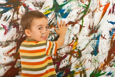 Happy kid painting with his palms a wall and looking back over shoulder Stock Photo - 12596522