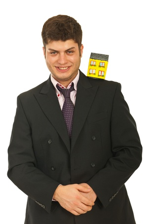 Happy business man holding miniature house on his shoulder isolated on white background photo