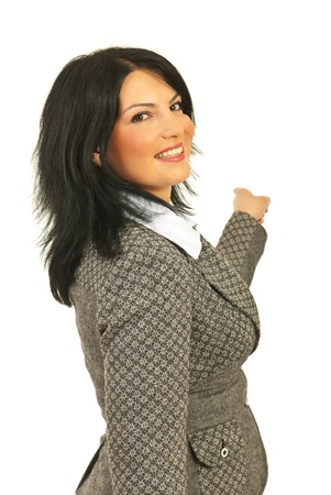 Happy business woman pointing to background and looking over shoulder isolated on white background photo
