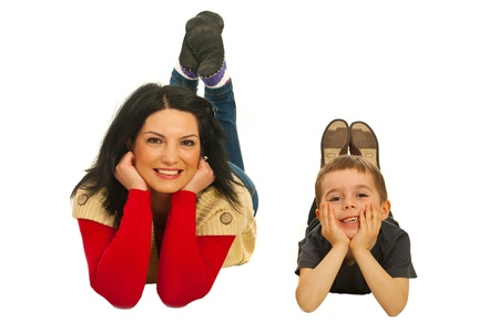 Cheerful mother and son lying together on floor isolated on white background photo