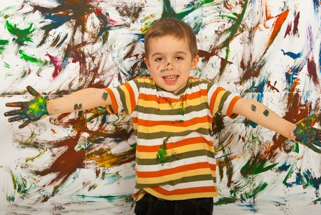Happy painter child boy standing with open arms in front of painted background Stock Photo - 12596578