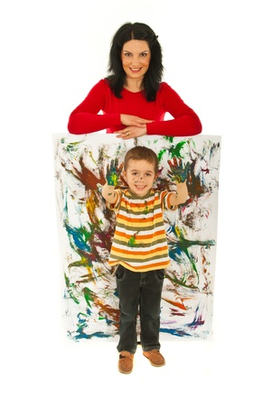 Happy mother resting hands on mini painted wall  while her son showing messy painted palms isolated onw hite background photo