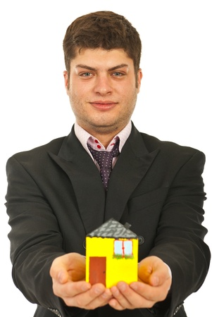 Business man giving miniature house isolated on white background photo