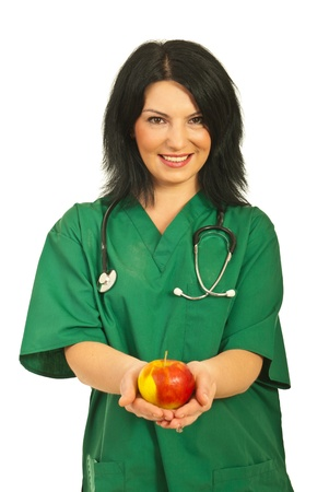 Smiling health worker woman offering apple isolated on white background photo