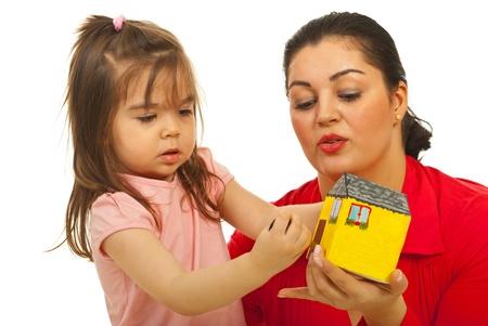 Close-up van moeder en dochter openen deur met de sleutel tot miniatuur huis op een witte achtergrond Stockfoto