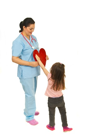 unifrom: Little girl offering heart shape to a smiling doctor woman isolated on white background Stock Photo