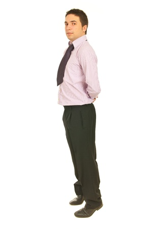taller: Businessman rising on tip toes to look taller and holding his hands to back isolated on white background