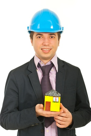 Architect man holding house miniature in his plam isolated on white background photo
